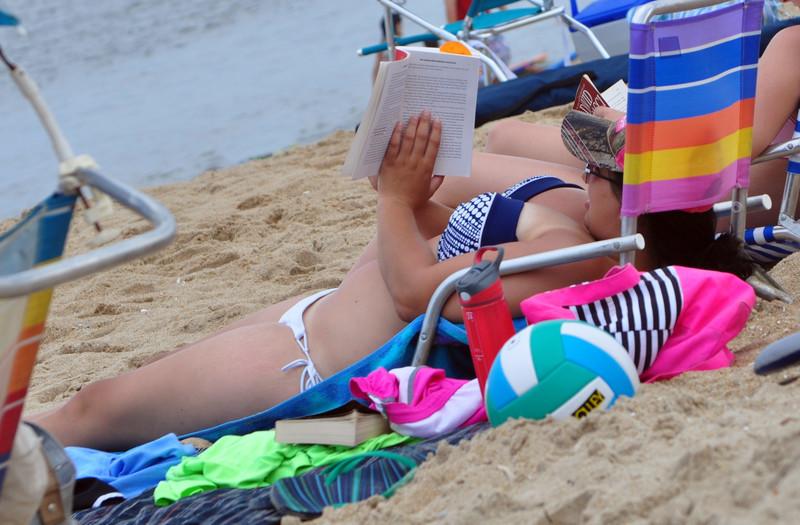 busty beach milf lady sunbathing & reading book