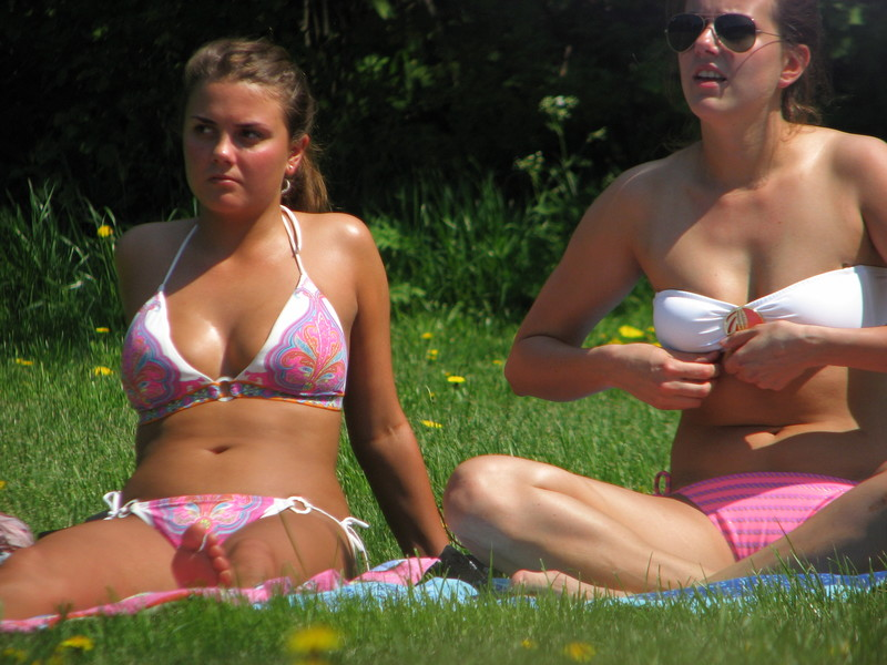 3 nice college girls tanning in a city park