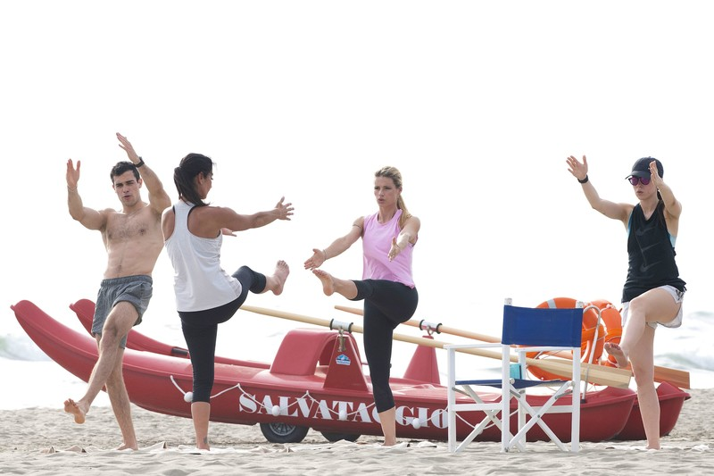 attractive babe Michelle Hunziker practices yoga on the beach